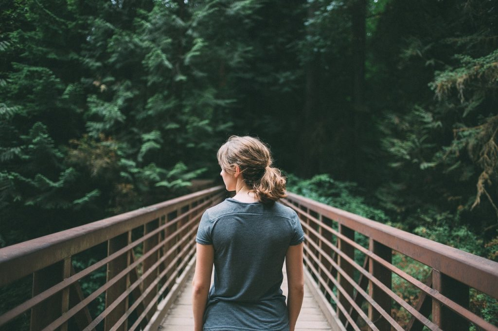 woman hiking across a bridge in the woods